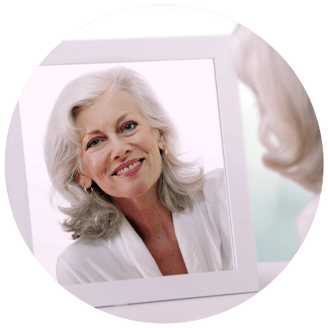 dental implant patient looking in mirror smiling seattle wa